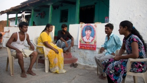 In this May 25, 2018 file photo, family members grieve by a portrait of Bala Krishna, a 33-year-old motorized rickshaw driver who was killed by a mob inflamed by social media in Jiyapalli village, outside his house at Korremula village, on the outskirts of Hyderabad, India.