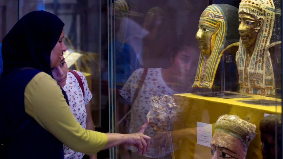 Visitors look at gold-plated wooden mummy masks that were confiscated by the Italian police months ago, and returned to Egypt, at the Egyptian Museum in Cairo, Egypt, Wednesday, July 4, 2018. (AP Photo/Amr Nabil)