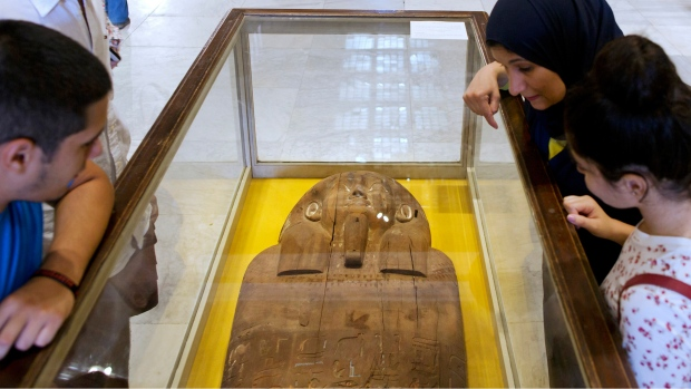 Visitors look at the lid of an artifact in Egypt
