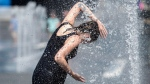 A woman cools down in a water fountain as she beats the heat in Montreal, Monday, July 2, 2018. THE CANADIAN PRESS/Graham Hughes