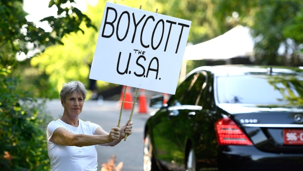 Elizabeth Gomes holds a sign calling for an American boycott as guests arrive at Lornado, the official residence of the U.S. Ambassador to Canada, for the Fourth of July Independence Day celebration in Ottawa on Wednesday, July 4, 2018. THE CANADIAN PRESS/Justin Tang