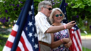 Robert Gordon and Mary Ellen Gordon take a photo beside historic American flags as they arrive at the Fourth of July Independence Daycelebration at Lornado, the ambassador's official residence, in Ottawa on Wednesday, July 4, 2018. THE CANADIAN PRESS/Justin Tang