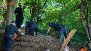 Members of the Toronto Police Service excavate the back of property along Mallory Cres. in Toronto after confirming they have found human remains during an investigation in relation to alleged serial killer Bruce McArthur on Thursday, July 5, 2018. THE CANADIAN PRESS/Tijana Martin