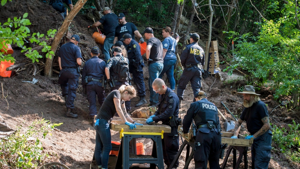 Members of the Toronto Police Service sift and excavate materials from the back of property along Mallory Cres. in Toronto after confirming they have found human remains during an investigation in relation to alleged serial killer Bruce McArthur on Thursday, July 5, 2018. (THE CANADIAN PRESS/Tijana Martin)