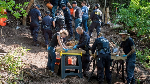 Members of the Toronto Police Service sift and excavate materials from the back of property along Mallory Cres. in Toronto after confirming they have found human remains during an investigation in relation to alleged serial killer Bruce McArthur on Thursday, July 5, 2018. THE CANADIAN PRESS/Tijana Martin