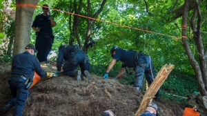 Members of the Toronto Police Service excavate the back of property along Mallory Cres. in Toronto on Thursday, July 5, 2018. THE CANADIAN PRESS/Tijana Martin