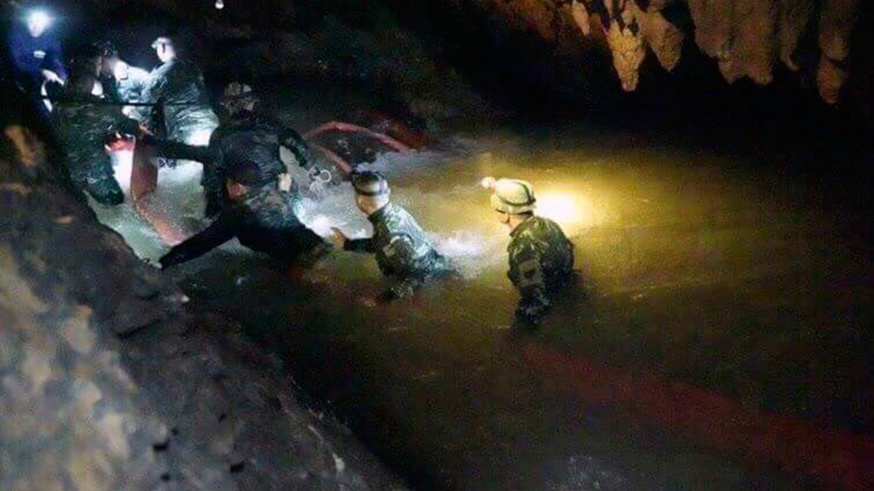 Thai rescue teams use headlamps to enter a pitch-black cave complex where 12 boys and their soccer coach went missing, in Mae Sai, Chiang Rai province, northern Thailand, Monday, July 2, 2018. (Tham Luang Rescue Operation Center via AP)
