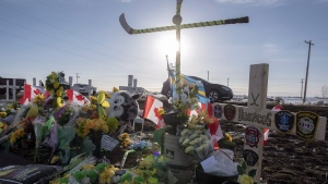 Hockey sticks, messages and other items continue to be added to a memorial at the intersection of a fatal bus crash that killed 16 members of the Humboldt Broncos hockey team last week near Tisdale, Sask. on Saturday, April 14, 2018. (THE CANADIAN PRESS/Liam Richards)