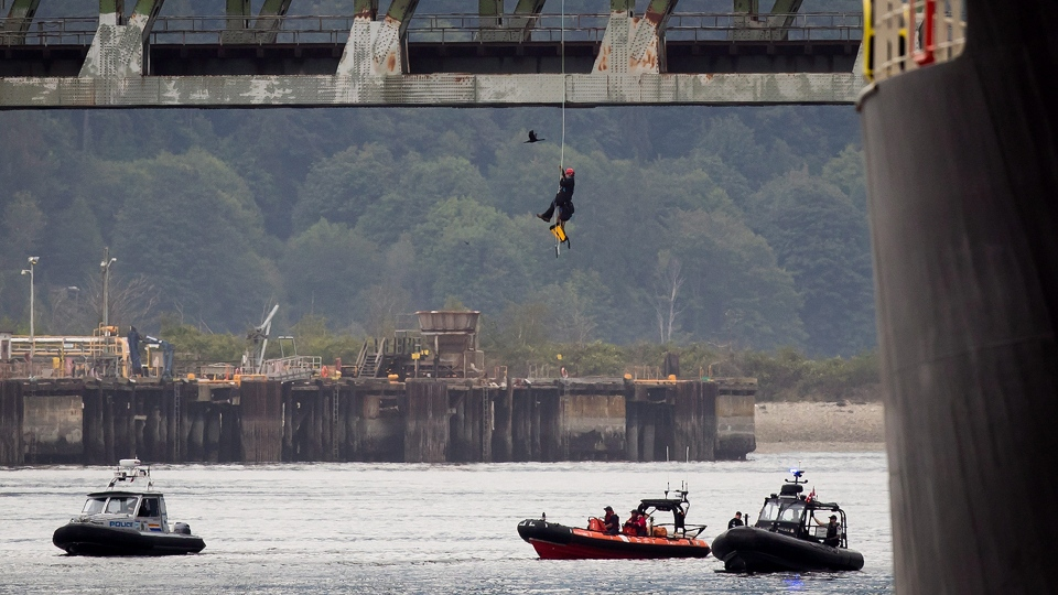 A protester opposed to the Kinder Morgan Trans Mountain pipeline expansion is lowered to a police boat after spending two days suspended from the Second Narrows Bridge in Vancouver on Wednesday July 4, 2018. THE CANADIAN PRESS/Darryl Dyck