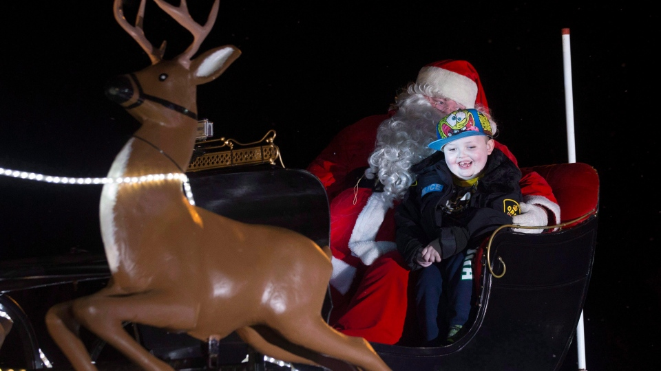 Evan Leversage rides in a sleigh at a Christmas Parade in St. George, Ontario on Saturday October 24, 2015. (THE CANADIAN PRESS/Chris Young)
