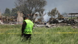 A police officer guards the perimeter around the wreckage of several fireworks workshops in Tultepec, Mexico, Thursday, July 5, 2018. (AP Photo/Emilio Espejel)