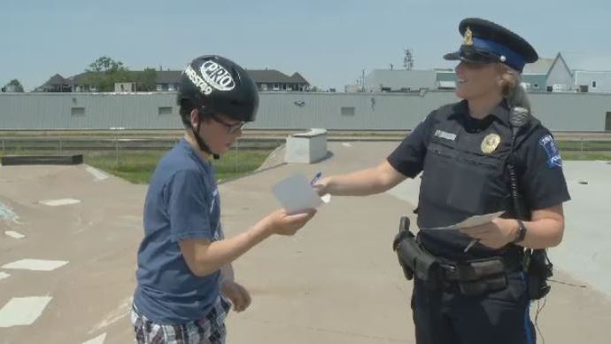An officer with the Truro Police Service hands out a ticket for good behaviour on July 5, 2018.