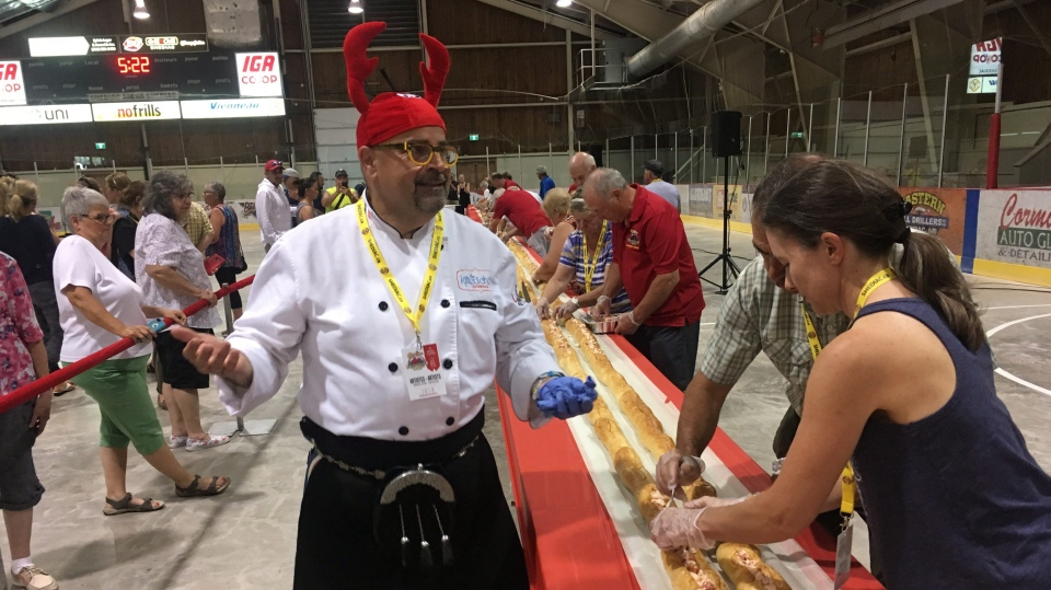 Chef Alain Bosse stands next to a lobster roll measuring measured just over 67 metres in Shediac, N.B., in this Wednesday, July 4, 2018 handout photo. (THE CANADIAN PRESS/HO - Shediac Lobster Festival)