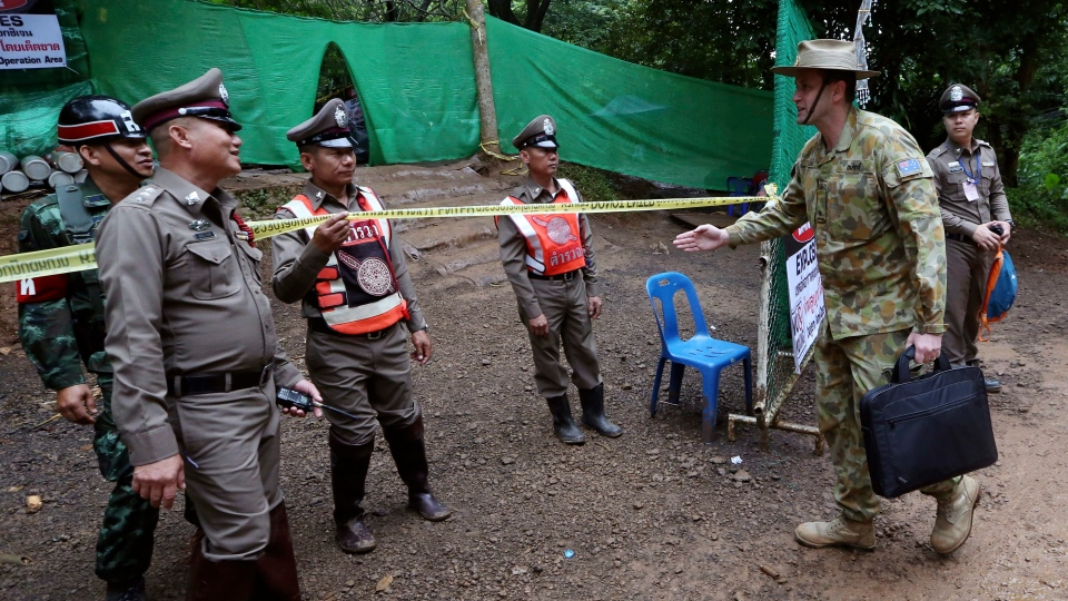 Australian Federal Police and Defense Force personnel arrive near a cave where 12 boys and their soccer coach have been trapped since June 23, in Mae Sai, Chiang Rai province, in northern Thailand Sunday, July 8, 2018. (AP Photo/Sakchai Lalit)