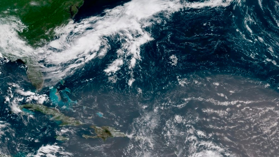 This geocolor image GOES-16 satellite image taken Sunday, July 8, 2018, at 15:00 UTC, shows Tropical Storm Chris, top left, off the U.S. East Coast. (NOAA via AP)