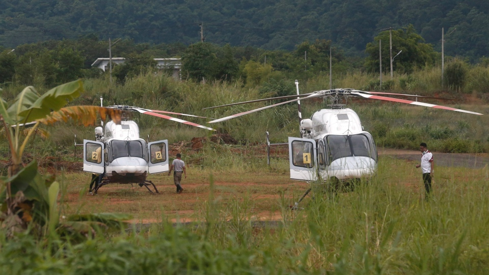 Two helicopters wait near the cave for more evacuations of the boys and their soccer coach who have been trapped since June 23, in Mae Sai, Chiang Rai province, northern Thailand Monday, July 9, 2018. (AP Photo/Sakchai Lalit)
