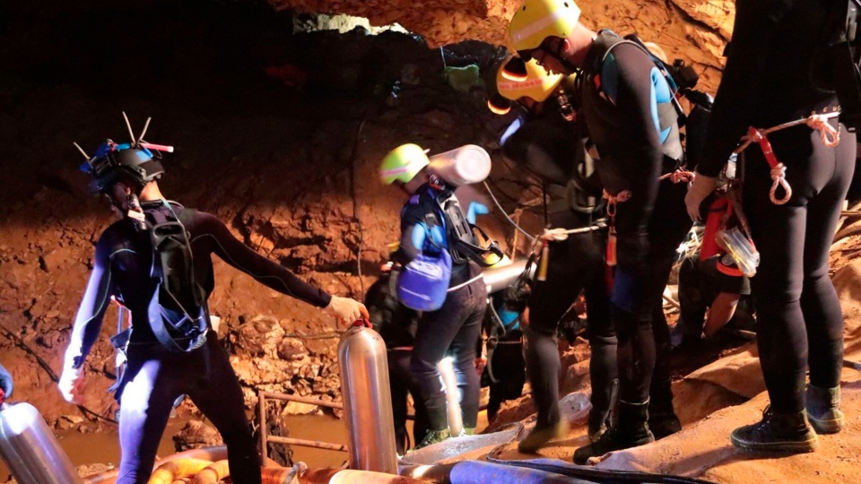 In this undated photo released by Royal Thai Navy on Saturday, July 7, 2018, Thai rescue team members walk inside a cave where 12 boys and their soccer coach have been trapped since June 23, in Mae Sai, Chiang Rai province, northern Thailand. Beware fake videos and photos purporting to be from the rescue mission. (Royal Thai Navy via AP)