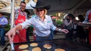 Alberta Premier Rachel Notley cooks pancakes as she attends her annual Stampede breakfast in Calgary on Monday, July 9, 2018. (THE CANADIAN PRESS/Jeff McIntosh)