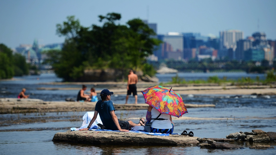 Linda and Jean of Gatineau, Quebec., sit on the banks of the Ottawa River and attempt to stay cool in Gatineau on Tuesday, July 16, 2013. (THE CANADIAN PRESS/Sean Kilpatrick)