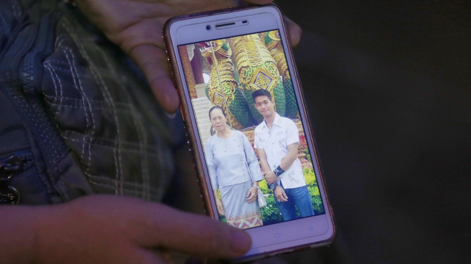 The aunt of coach Ekapol Chantawong shows a picture of the coach and his grandmother on a mobile phone screen, in Mae Sai, Chiang Rai province, in northern Thailand, Wednesday, July 4, 2018. (AP Photo/Sakchai Lalit)