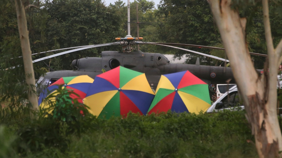 Local police place umbrellas around an evacuation helicopter as the remaining trapped boys and their coach are extracted from a cave in Mae Sai, Chiang Rai province, northern Thailand on Tuesday, July 10, 2018. (AP / Sakchai Lalit)