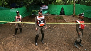 Thai policemen stand guard near a cave where 12 boys and their soccer coach have been trapped since June 23, in Mae Sai, Chiang Rai province, in northern Thailand Sunday, July 8, 2018. (AP Photo/Sakchai Lalit)
