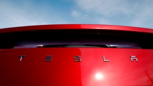 In this April 15, 2018, file photo, the sun shines off the rear deck of a roadster on a Tesla dealer's lot in the south Denver suburb of Littleton, Colo. (AP Photo/David Zalubowski)