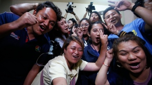 Thai media celebrate after evacuation in Chiang Rai as divers evacuated some of the 12 boys and their coach trapped at Tham Luang cave in the Mae Sai district of Chiang Rai province, northern Thailand, Tuesday, July 10, 2018. Thai Navy SEALs say all 12 boys and their coach were rescued from the cave, ending an ordeal that lasted more than 2 weeks. (AP Photo/Sakchai Lalit)