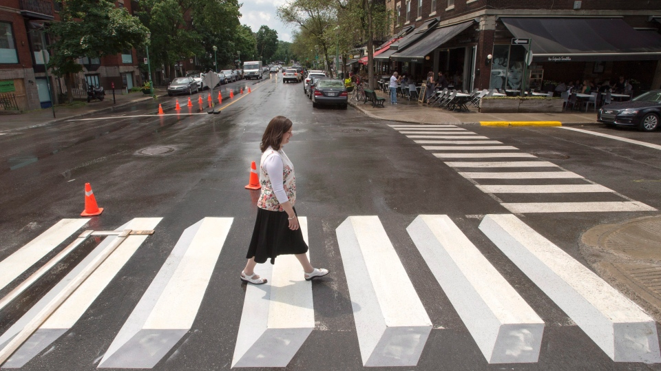 A pedestrian walks a crosswalk painted in a three-dimensional style for a pilot project, in the Montreal borough of Outremont on Tuesday, July 10, 2018. (THE CANADIAN PRESS/Ryan Remiorz)
