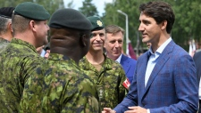"Prime Minister Justin Trudeau, right, speaks to troops as he visits Adazi Military Base in Kadaga, Latvia, on Tuesday, July 10, 2018. Trudeau says he hopes the upcoming NATO summit will send a message of broad support for unity and solidarity but acknowledges that there will ""no doubt be calls for greater investments in defense spending"", a key issue that is badly dividing the military alliance.(AP / Roman Koksarov)"