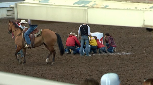 Crews attend to Obrey Motowylo after he was thrown from his chuckwagon during the eighth heat of the Rangeland Derby on Tuesday, July 10, 2018