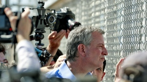 New York City Mayor Bill de Blasio looks through a closed gate at the Port of Entry facility, in Fabens, Texas, where tent shelters are being used to house separated family members on Thursday, June 21, 2018. (AP Photo/Matt York)