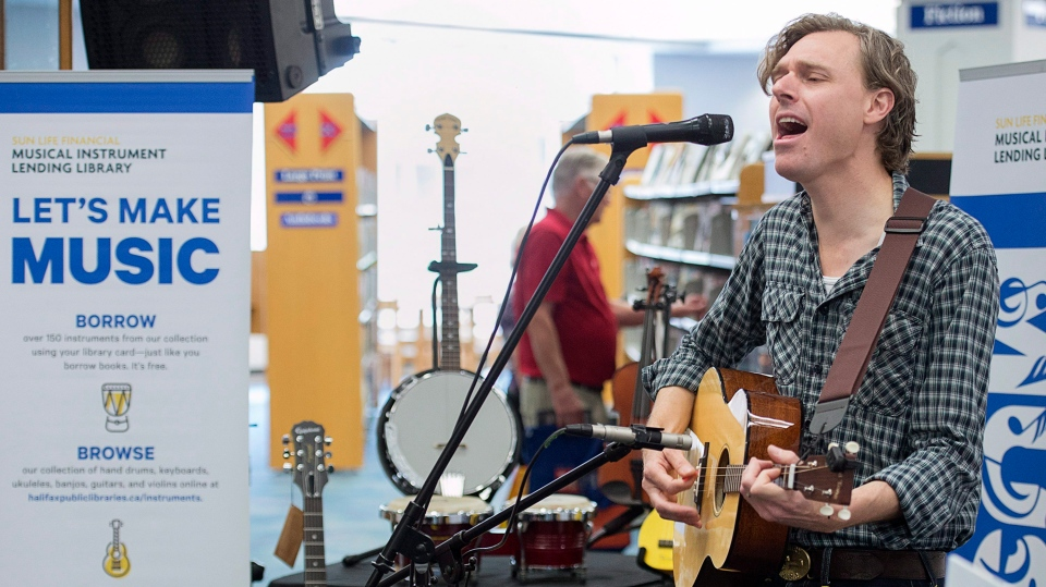 Joel Plaskett plays a tenor guitar as he participates the launch of a musical instruments lending program at the Halifax Public Library in Dartmouth, N.S., on Wednesday, July 11, 2018. (THE CANADIAN PRESS/Andrew Vaughan)