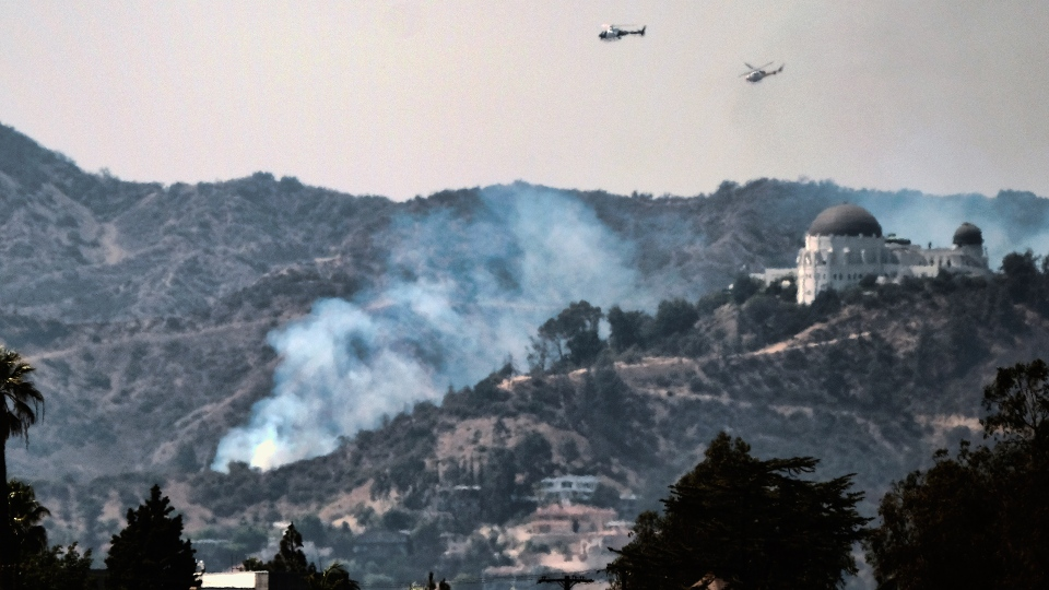 Water dropping helicopters fly over the Griffith Observatory in Los Angeles as a wildfire burns along the hillsides sending up huge plumes of smoke visible throughout the city Tuesday, July 10, 2018. (AP / Richard Vogel)