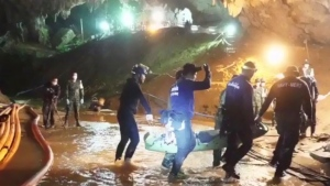 This undated from video released via the Thai NavySEAL Facebook Page on Wednesday, July 11, 2018, shows rescuers hold an evacuated boy inside the Tham Luang Nang Non cave in Mae Sai, Chiang Rai province, in northern Thailand. (Thai NavySEAL Facebook Page via AP)