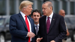 U.S. President Donald Trump, left, talks with Turkey's President Recep Tayyip Erdogan, right, as they arrive together for a family photo at a summit of heads of state and government at NATO headquarters in Brussels on Wednesday, July 11, 2018. (AP Photo/Pablo Martinez Monsivais)