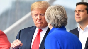 U.S. President Donald Trump, left, clenches a fist when talking to British Prime Minister Theresa May during a summit of heads of state and government at NATO headquarters in Brussels on Wednesday, July 11, 2018. (AP Photo/Geert Vanden Wijngaert)