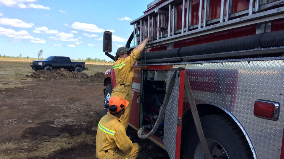 Fire crews in Ramara Township, Ont. work to extinguish a grass fire on Wednesday, July 11, 2018.  (Rob Cooper/CTV News)