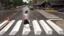 A pedestrian walks a crosswalk painted in a 3-dimensional style for a pilot project, in the Montreal borough of Outremont on Tuesday, July 10, 2018. THE CANADIAN PRESS/Ryan Remiorz