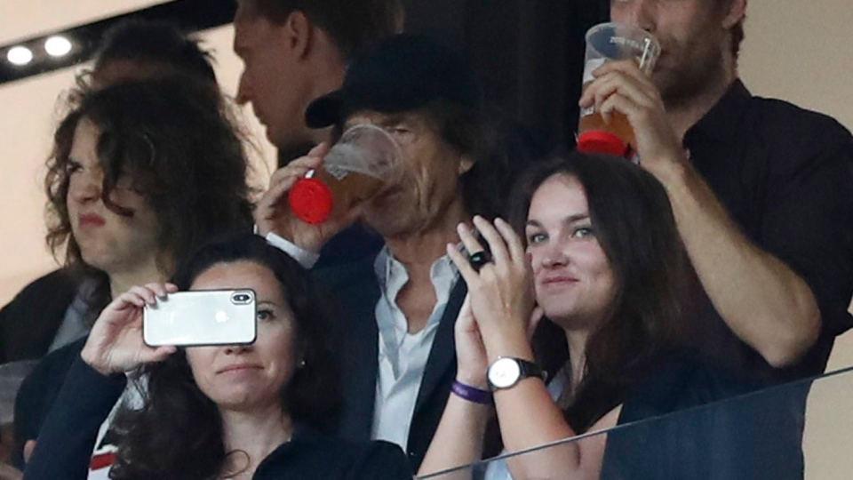 Singer Mick Jagger of the Rolling Stones, in black baseball hat, drinks a pint during the semifinal match between Croatia and England at the 2018 soccer World Cup in the Luzhniki Stadium in, Moscow, Russia, Wednesday, July 11, 2018. (AP Photo / Alastair Grant)