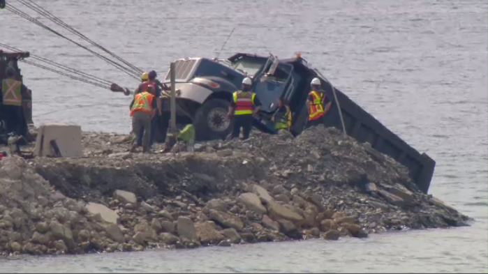 A fleet of tow trucks helps to remove a dump truck from the water at the site of a workplace fatality in Halifax on July 11, 2018.