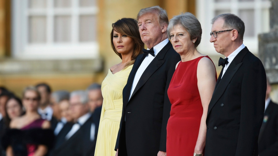 British Prime Minister Theresa May accompanied by her husband Philip, right, stand with U.S. President Donald Trump, and first lady Melania Trump, before a black tie dinner at Blenheim Palace, in Blenheim, England, Thursday, July 12, 2018. (Geoff Pugh / Pool via AP)