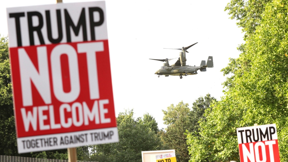 A helicopter leaves the grounds of the US ambassador residence in Regent's Park, London, while demonstrators protest against the visit of U.S. President Donald Trump Thursday July 12, 2018. (Gareth Fuller/PA via AP)