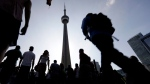 People make their way towards the CN Tower and Rogers Centre for the opening ceremony in the Pan Am Games in Toronto, Friday, July 10, 2015. (AP / Gregory Bull)