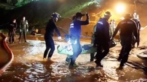 This undated from video released via the Thai NavySEAL Facebook Page on Wednesday, July 11, 2018, shows rescuers hold an evacuated boy inside the Tham Luang Nang Non cave in Mae Sai, Chiang Rai province, in northern Thailand. (Thai Navy SEAL Facebook Page via AP)