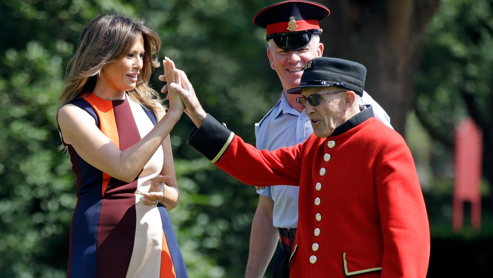 U.S. First Lady Melania Trump high-fives with a British military veteran known as a 'Chelsea Pensioner' during a game of bowls at The Royal Hospital Chelsea in central London Friday, July 13, 2018. (AP Photo/Luca Bruno, Pool)