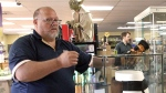 """In this May 2, 2018 file photo, Blockbuster Alaska General Manager Kevin Daymude moves a display case featuring the jockstrap worn by actor Russell Crowe in the 2005 movie """"Cinderella Man"""" at a Blockbuster video store in Anchorage, Alaska. (AP Photo/Mark Thiessen, File)"""