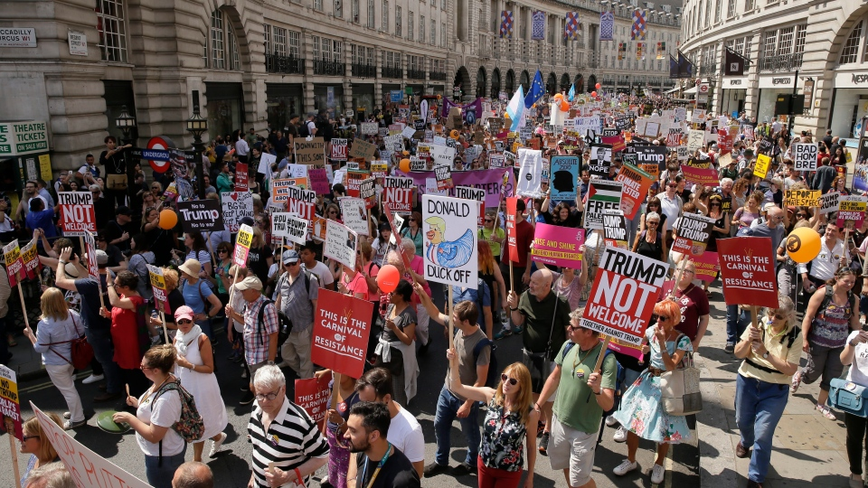 Protestors hold banners during the 'Stop Trump' Women's March in London, Friday, July 13, 2018. (AP Photo/Tim Ireland)