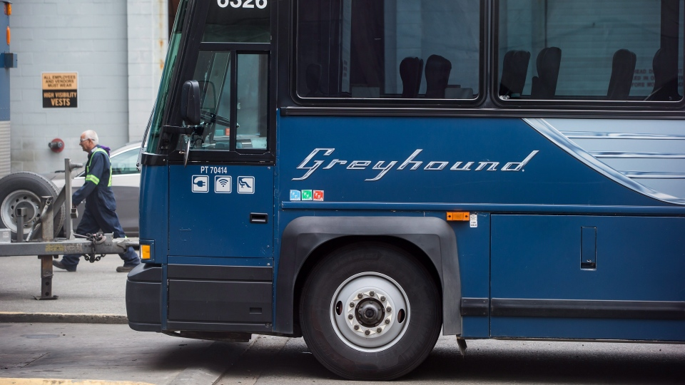 A worker walks past a Greyhound bus sitting idle, in Vancouver, on Monday July 9, 2018. THE CANADIAN PRESS/Darryl Dyck