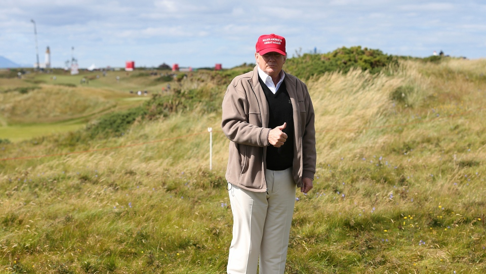 In this July 30, 2015, then-presidential contender Donald Trump gestures to the media on the 17th fairway on the first day of the Women's British Open golf championship on the Turnberry golf course in Turnberry, Scotland. (AP Photo/Scott Heppell, File)